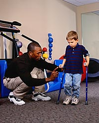 Picture of young boy, with canes, during a physical therapy session