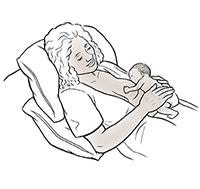 Woman breastfeeding premature baby in laid-back position.