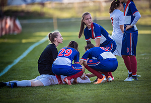 Group of female soccer players and referee gathering around injured player on playing field.
