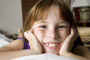 A girl smiles on a bed indoors.
