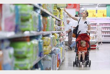 Women pushing a stroller with a baby down a grocery store aisle