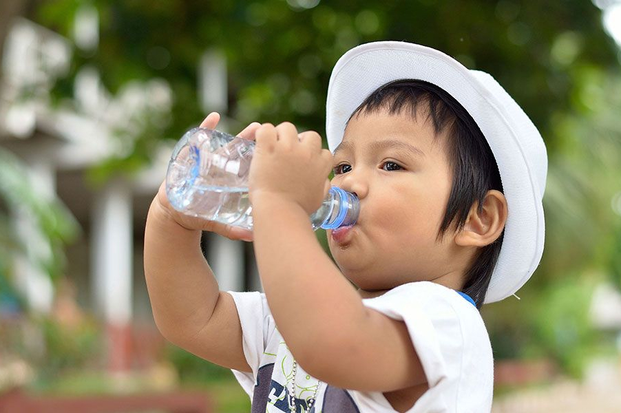Toddler wearing a hat drinking from a plastic water bottle