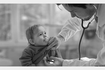 Doctor using stethoscope to listen to baby's heart