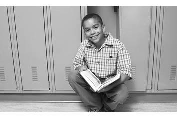 Child squatting by locker, reading a book