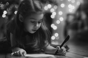 Little girl writing a list while laying by a Christmas tree