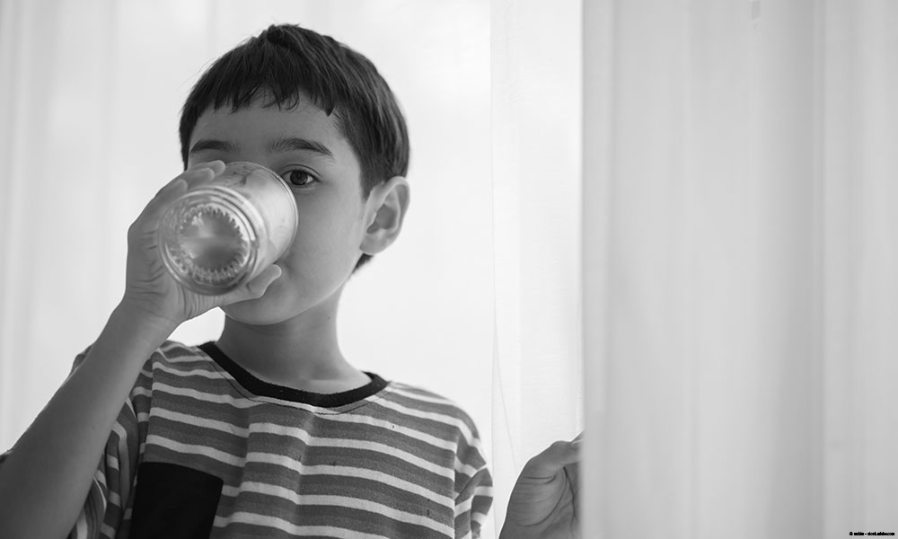 Little boy drinking a glass of water.