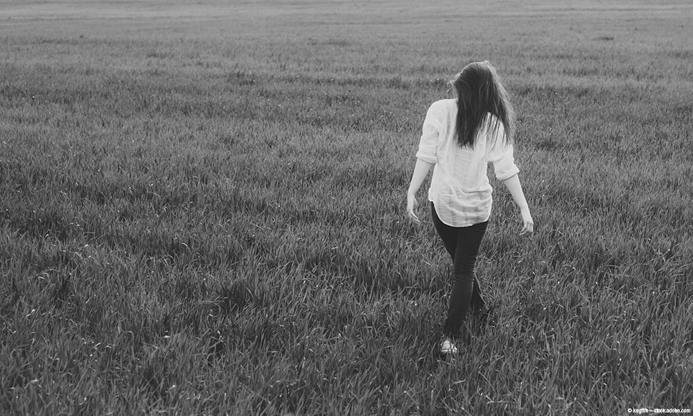 Teenage girl walking through a field of grass.
