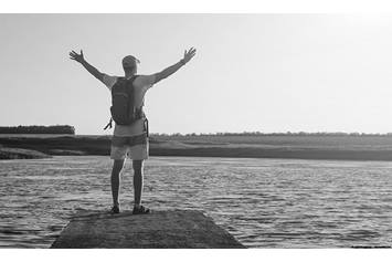 image of a man standing near water with his arms outstretched