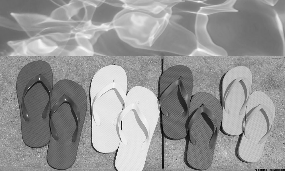 image of pairs of flip flops next to a swimming pool