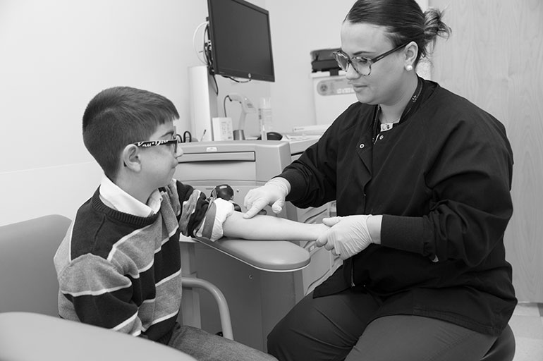 image of boy getting blood drawn in a lab