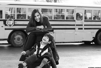 image of a teen girl standing and a boy sitting in a wheelchair next to a school bus