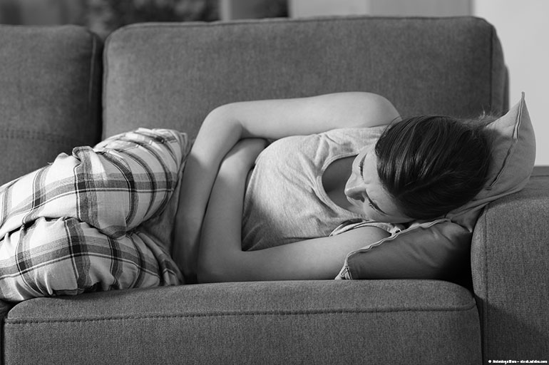 image of girl lying on a couch holding her stomach