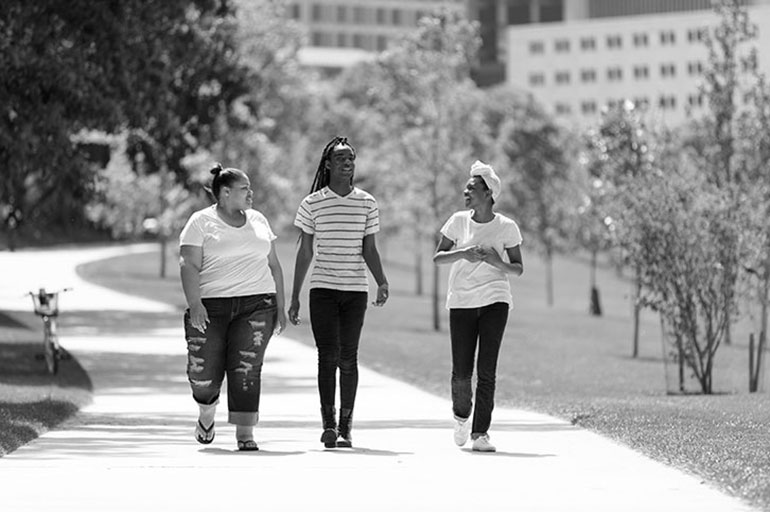 image of three teens walking in a park