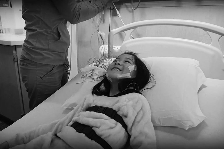 image of a girl in a hospital bed with electrodes attached to her face