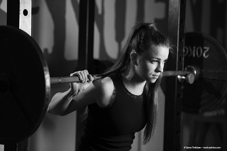 Teenage girls squatting with barbell