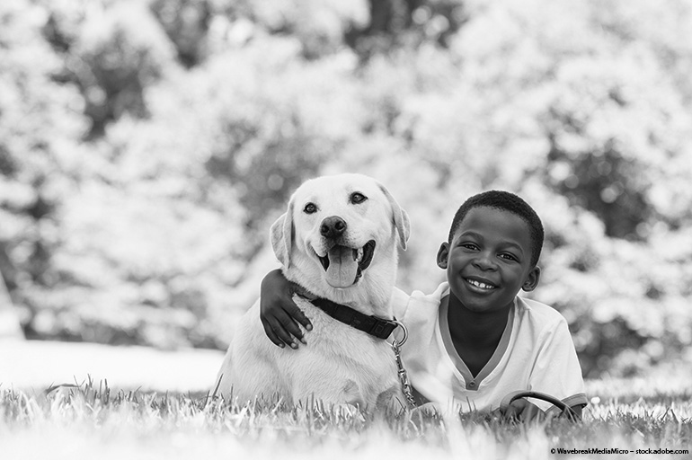Little boy and dog sitting in the grass