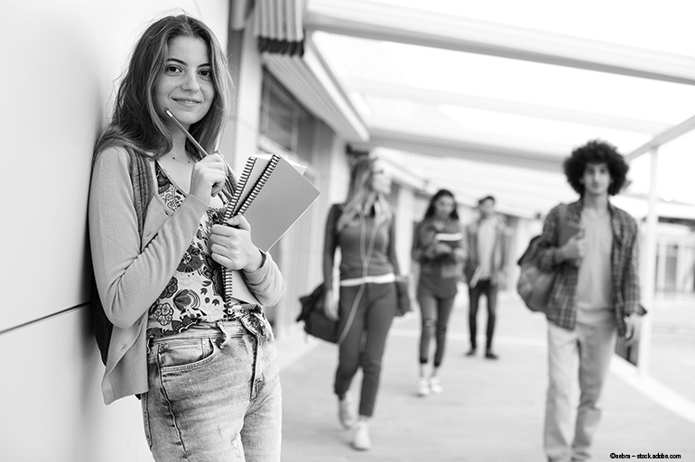 Teenage girl holding a book on a busy college campus