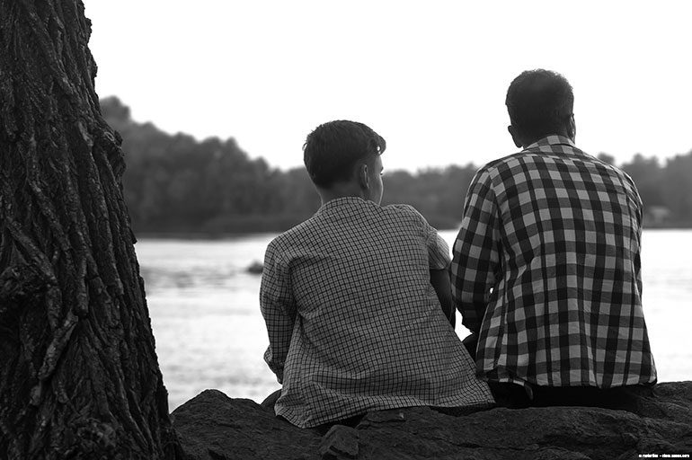 Two people sitting by a body of water