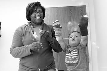 Nurse blowing bubbles for burn patient