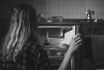 Teenage girl looking into the refrigerator