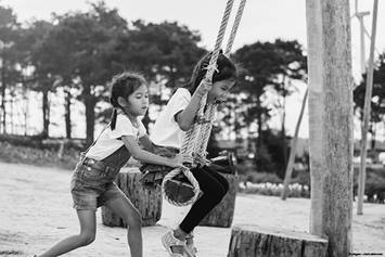 One kid pushing another kid on a swing set