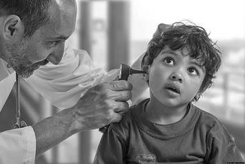 Doctor examining child's ear