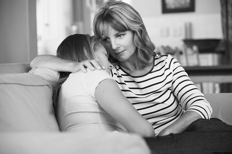 Mother comforting sad daughter on couch