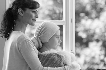 Child with cancer wearing headscarf, looking out the window with their mom