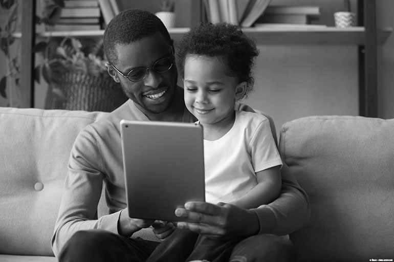 Child sitting on dad's lap looking at tablet