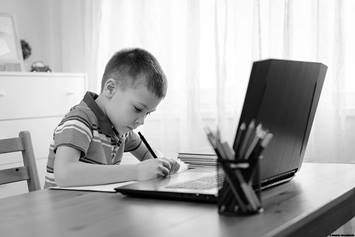 Child doing schoolwork at laptop
