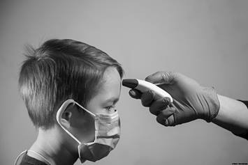 Child wearing a mask having his temperature taken