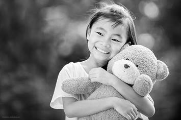 Little girl hugging teddy bear