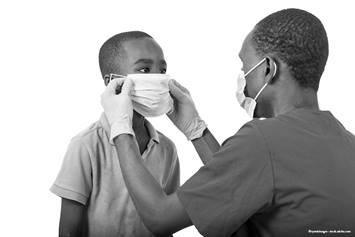 Medical professional helping a child put on a mask