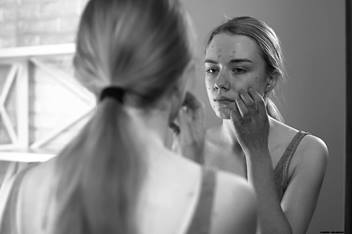 Teenager girl looking in the mirror touching her face