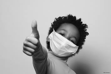 Little boy wearing a face mask giving a thumbs up