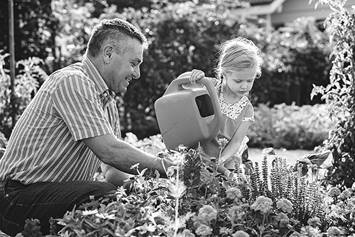 Father and daughter watering plants