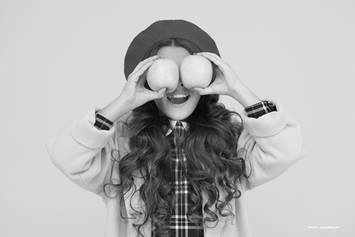 Girls holding two apples over her eyes
