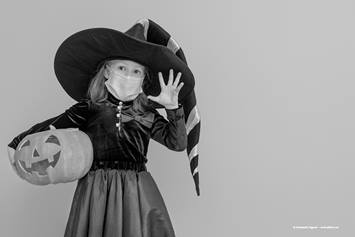 Little girl dressed up as a witch, wearing a face covering