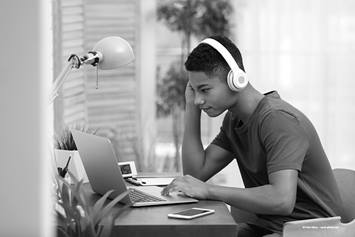 Teen wearing headphones and working on laptop
