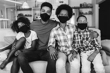 Family of four wearing face masks