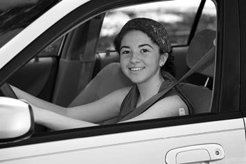 teen in the drivers seat on a car, her hands on the wheel