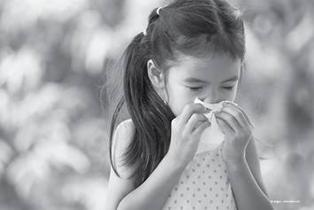 Little girl blowing her nose with a tissue.