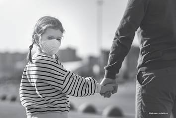 child wearing a mask holding an adult's hand