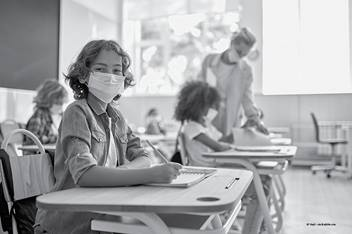 Child wearing mask sitting at desk in classroom