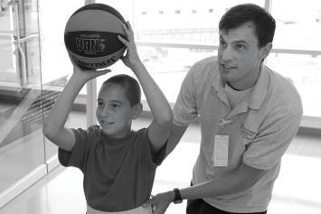 Young rehab patient shooting hoops with a therapist