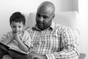 Father Reading to Young Boy in Hospital Room