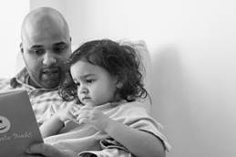 Dad reading to young girl in hospital room