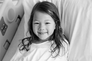 Young Girl Smiling in Hospital Bed