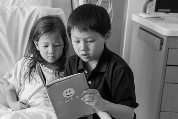 Young girl in hospital bed with older brother reading to her