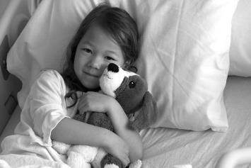 Young Girl in Hospital Bed with Stuffed Animal